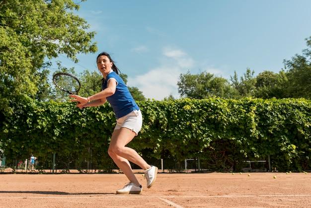 Jugadora de tenis con su raqueta Foto gratis