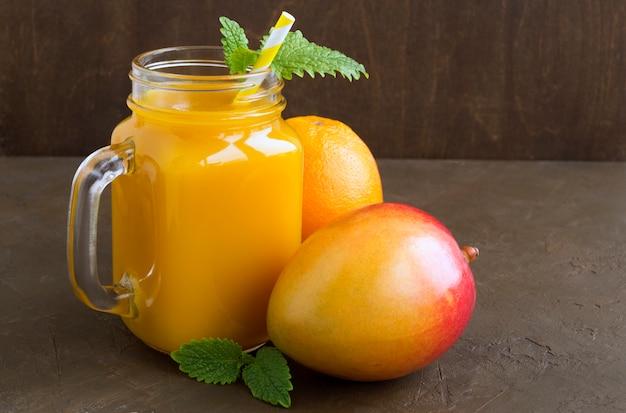 Jugo de fruta fresca en la jarra. en el fondo oscuro Foto Premium