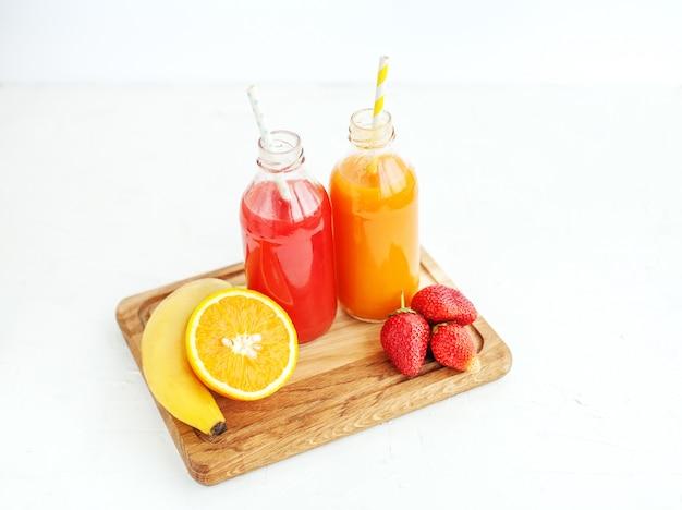 Jugo de frutas en botellas. plátano, naranja y fresas. verano y fiesta. Foto Premium