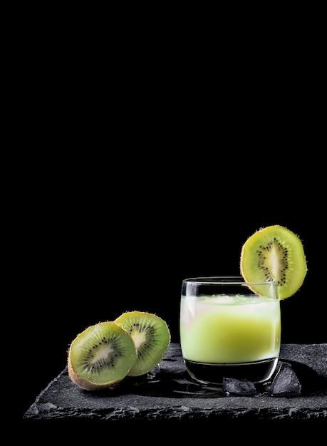 Jugo de kiwi con hielo sobre fondo negro y dos piezas de kiwi Foto Premium