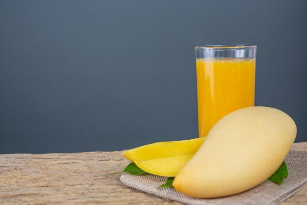 Jugo de mango en la mesa del piso de madera. Foto gratis