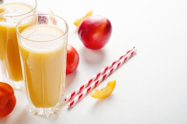 Jugo de melocotones y nectarinas con pulpa con frutas frescas sobre un fondo blanco. Foto Premium