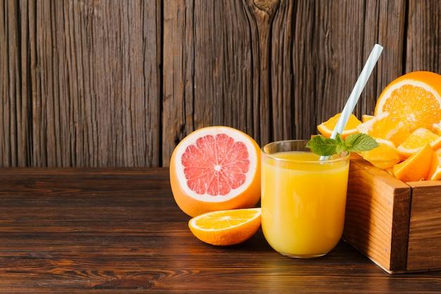 Jugo de naranja y pomelo sobre fondo de madera Foto gratis