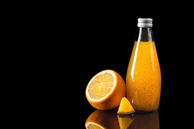 Jugo de naranja sobre fondo negro Foto gratis