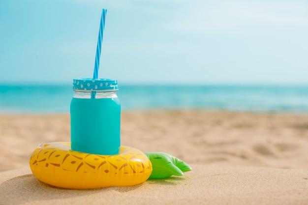 Jugo de piña con un inflable en la playa. Foto gratis