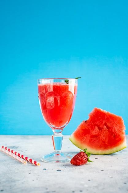 Jugo de sandía en vaso con fresa en la parte superior Foto gratis
