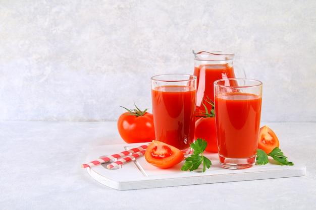 Jugo de tomate en vasos y una jarra sobre una mesa de concreto gris. Foto Premium