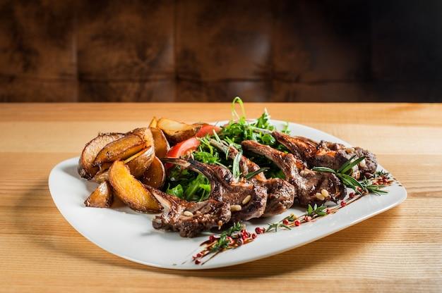 Jugosas costillas a la parrilla, cocinadas con vegetales y romero Foto Premium