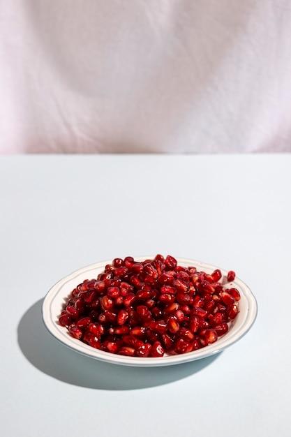 Jugosas semillas de granada en placa Foto gratis
