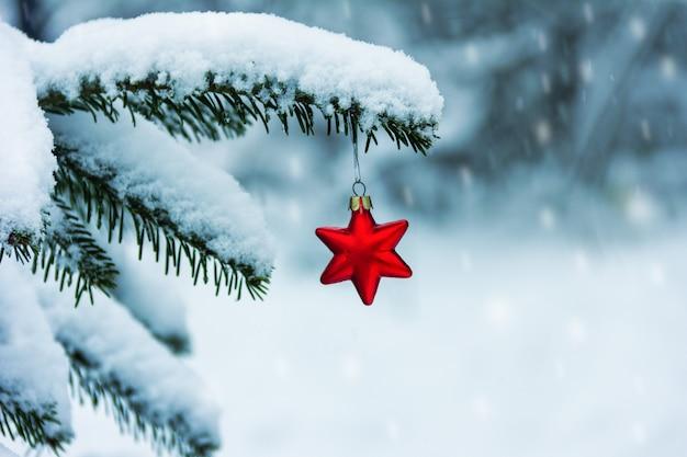 Juguete de árbol de navidad rojo con forma de estrella en una rama nevada del árbol de navidad y copos de nieve cayendo en un frío día de invierno Foto Premium