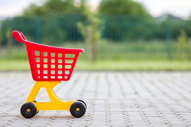 Juguete colorido plástico brillante del carro de compras al aire libre en día de verano soleado. Foto Premium