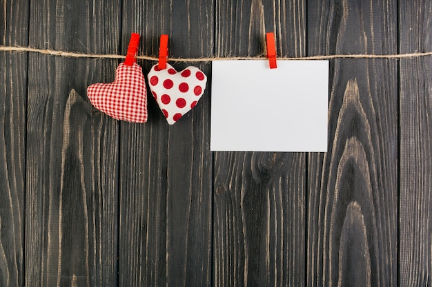 Juguetes de corazon colgando de una cuerda con tarjeta en blanco Foto gratis