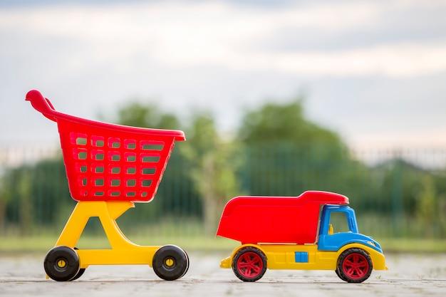 Juguetes de plástico de colores brillantes para niños al aire libre en un día soleado de verano. carro de carro y carrito de compras. Foto Premium