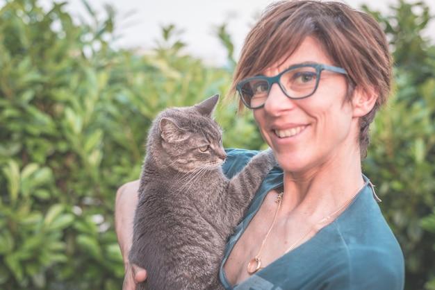 Juguetón gato doméstico sostenido y abrazado por una mujer sonriente con anteojos Foto Premium