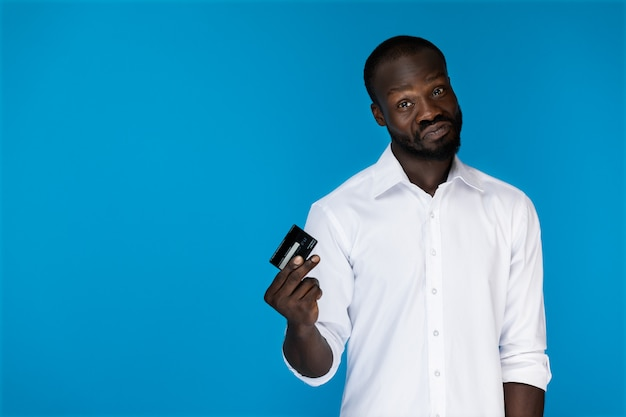 Juguetón mirando hacia adelante hombre afroamericano en camisa blanca tiene tarjeta de crédito en la mano derecha Foto gratis