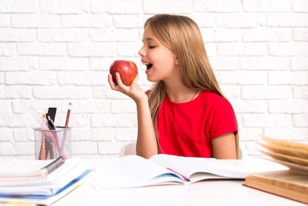 Juguetona colegiala mordiendo manzana Foto gratis