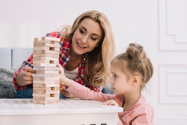 Juguetona madre e hija en sala Foto gratis