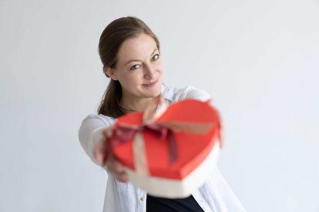 Juguetona mujer muy joven dando caja de regalo en forma de corazón Foto gratis
