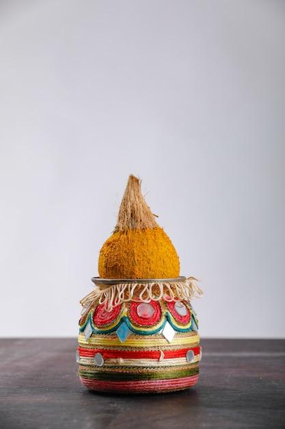 Kalash decorativo con coco y hoja con decoración floral. Foto Premium