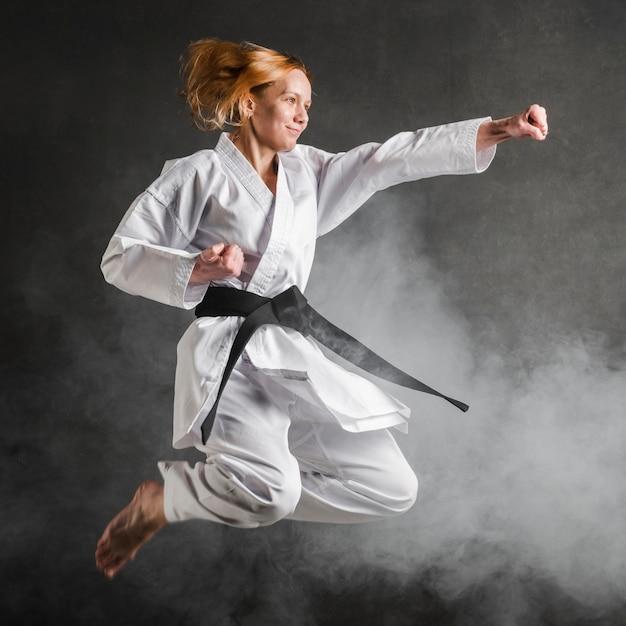 Karate mujer saltando tiro completo Foto gratis