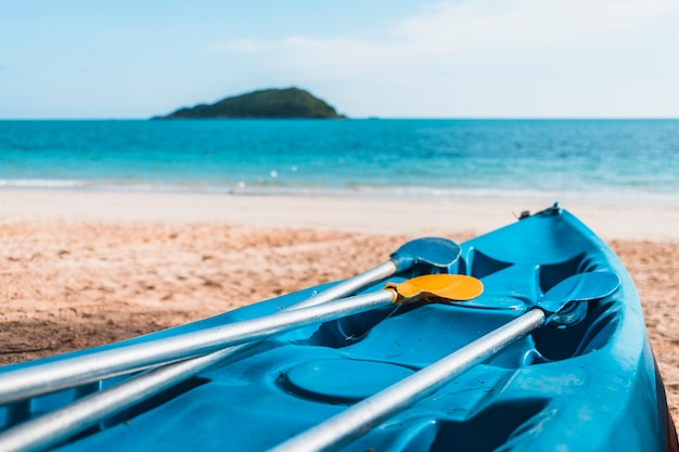 Kayak azul en la orilla del mar de arena Foto gratis