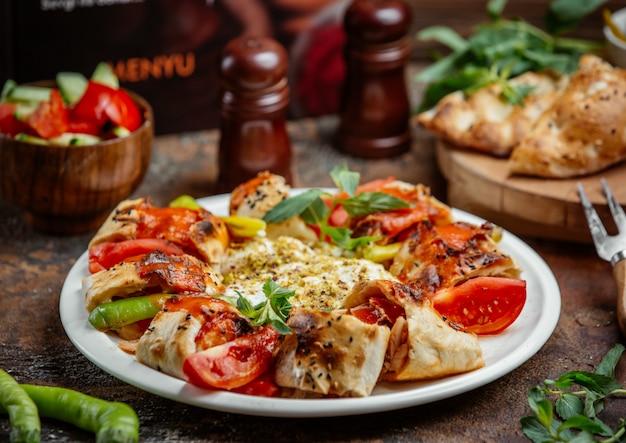 Kebab envuelto en beyti cubierto con salsa de tomate, servido con tomate, pimiento y yogur Foto gratis
