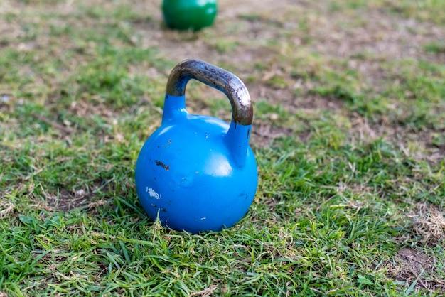 Kettlebell en el césped para ejercicios de fuerza al aire libre. Foto Premium