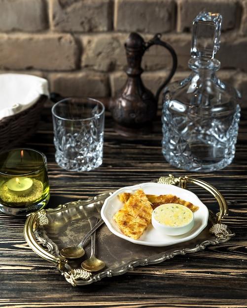 Khachapuri de queso con salsa sobre la mesa Foto gratis