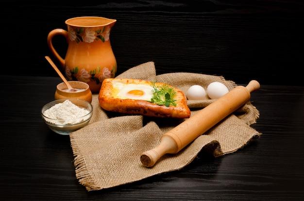 Khachapuri sobre tela de saco, rodillo, harina, huevos y jarra sobre un fondo negro Foto Premium