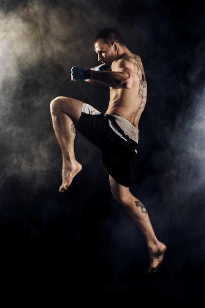 Kickbox muscular o luchador de muay thai golpeando en salto. fumar Foto Premium