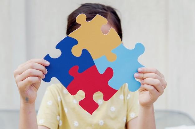 Kid niña manos sosteniendo rompecabezas rompecabezas, concepto de salud mental, día mundial de concienciación sobre el autismo Foto Premium