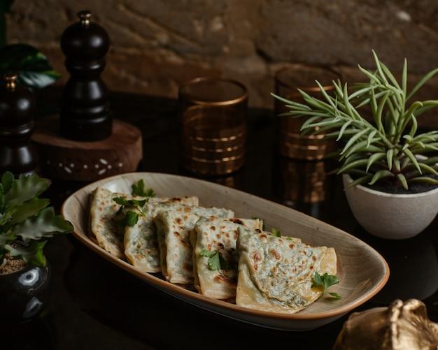 Kutab azerbaiyano, gozleme finamente asado y servido en un plato largo de cerámica Foto gratis