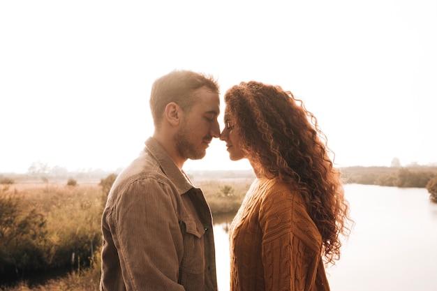 De lado feliz pareja teniendo un momento de ternura. Foto gratis