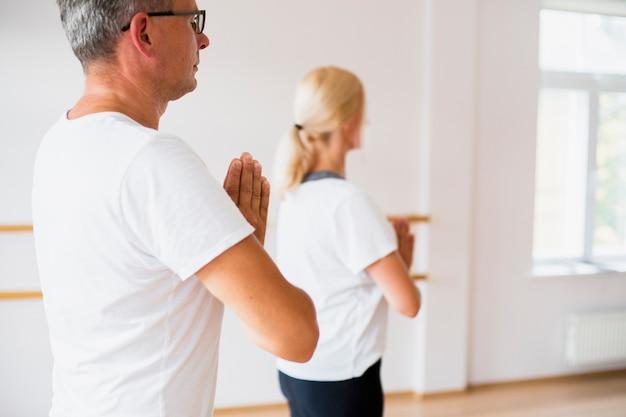 De lado hombre y mujer practicando yoga Foto gratis