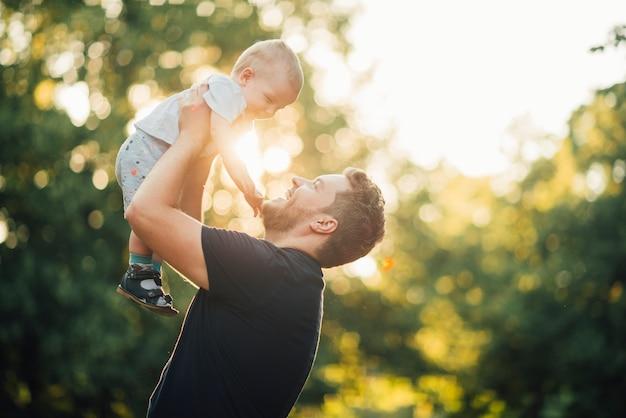 De lado el padre sonriéndole a su hijo Foto gratis