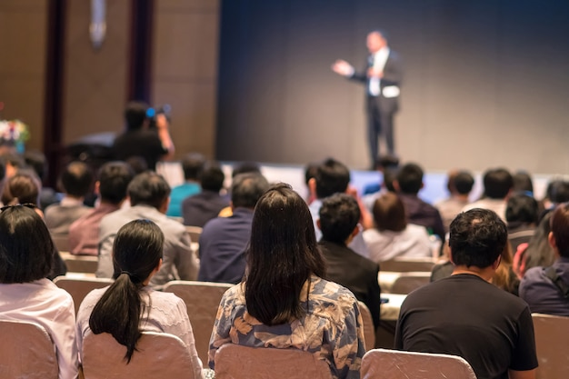 Lado posterior de audiences sentado y escuchando los speackers en el escenario Foto Premium