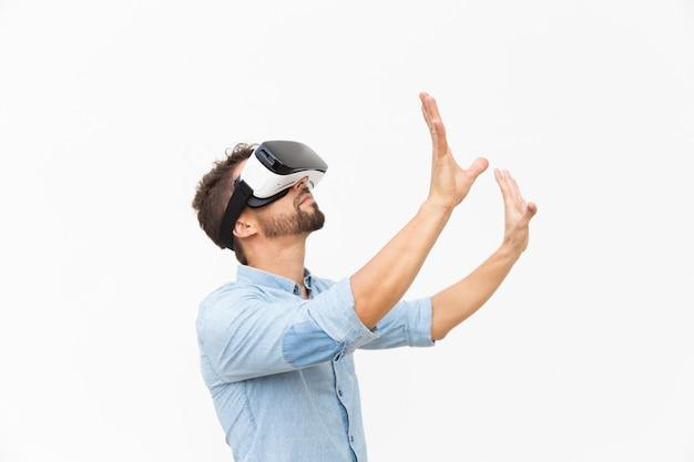 Lado del tipo barbudo con gafas de realidad virtual, tocando el aire Foto gratis