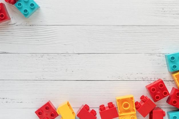 Ladrillos plásticos del constructor en el fondo de madera blanco. juguetes populares espacio libre para texto Foto Premium