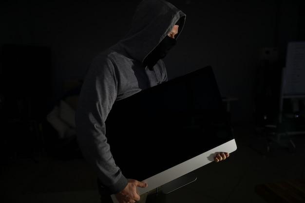 Ladrón en balaclava lleva pc del departamento de víctimas Foto Premium