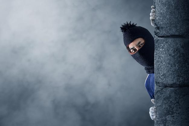 Ladrón escondido detrás de una pared vacía con espacio para texto Foto Premium