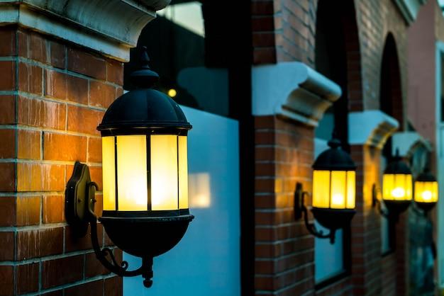 Lámpara contra una pared de ladrillo rojo en la noche. Foto gratis