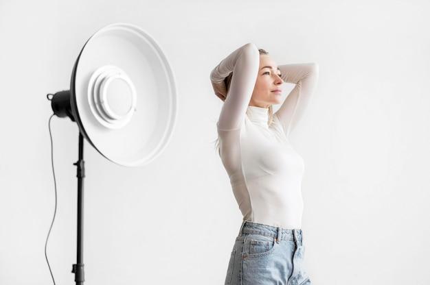 Lámpara de estudio y mujer sosteniendo su cabeza Foto gratis