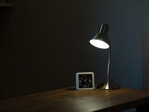 Lámpara y reloj en el cuarto oscuro con concepto de luz y sombra ...