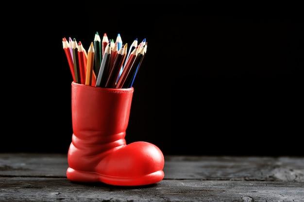 Lápices de colores en una bota roja en Foto Premium