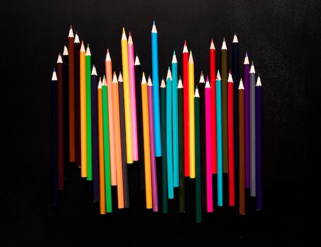 Lápices de colores brillantes colocados sobre fondo negro Foto gratis