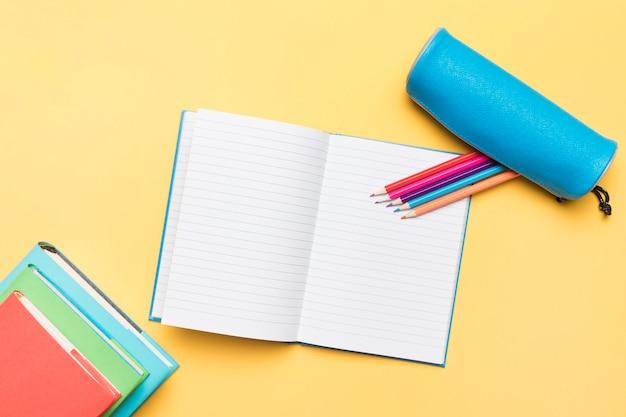 Lápices de colores compuestos en cuaderno abierto con páginas vacías Foto gratis