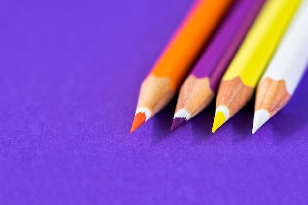 Lápices de colores sobre un fondo violeta con espacio para texto. Foto Premium