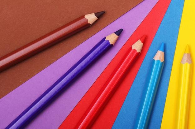Lápices sobre papel de colores. Foto gratis