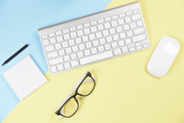Lápiz; bloc de notas adhesivo; los anteojos; teclado y ratón inalámbricos sobre fondo azul y amarillo. Foto gratis