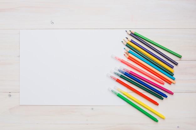 Lápiz colorido y rotulador con papel blanco blanco Foto gratis
